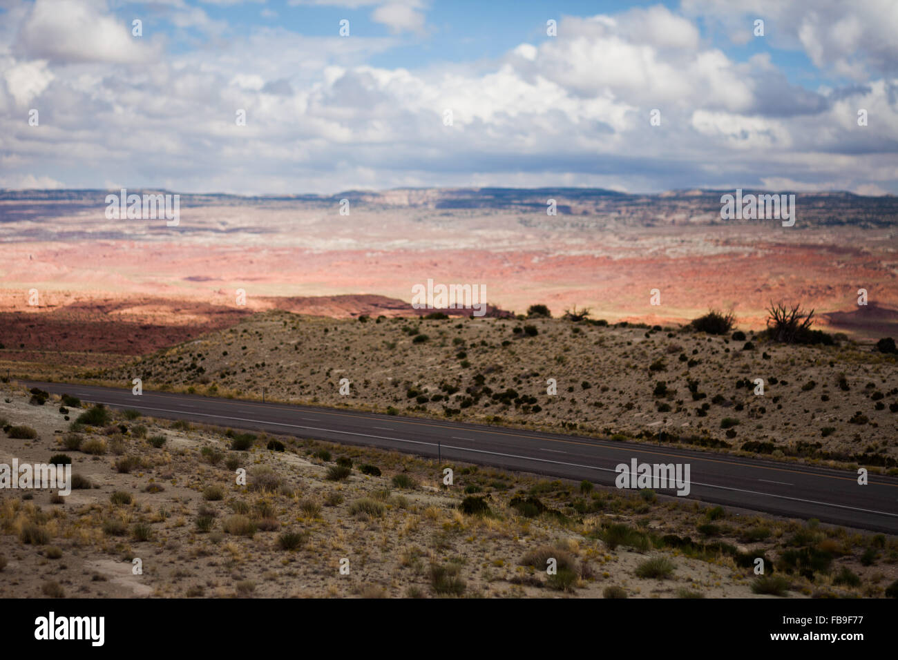 Highway through the desert with partly cloudy sky, Utah - Stock Image