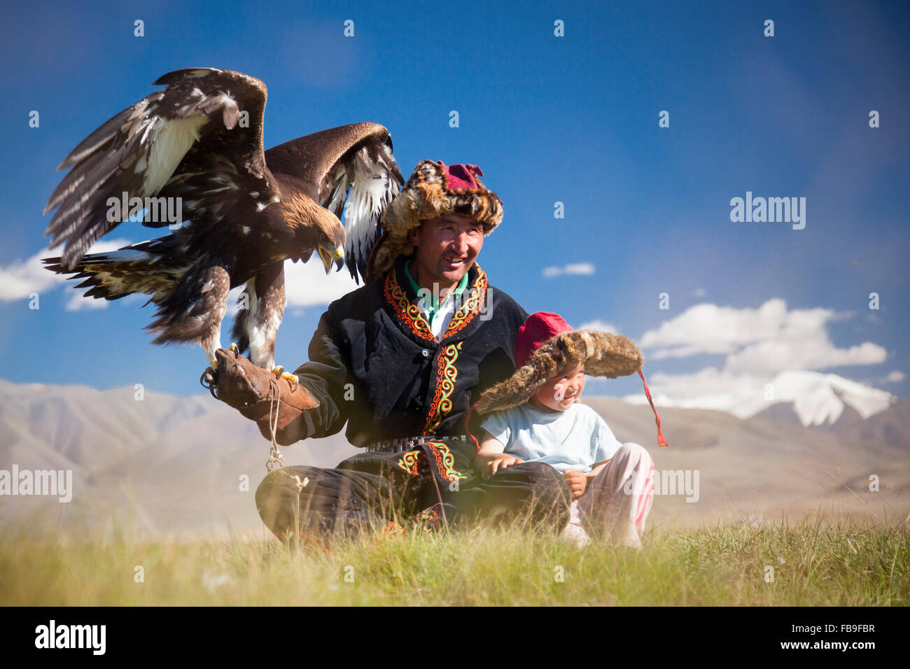 A Kazakh eagle hunter and son in the Tsaast Uul Valley, far-western Mongolia. - Stock Image