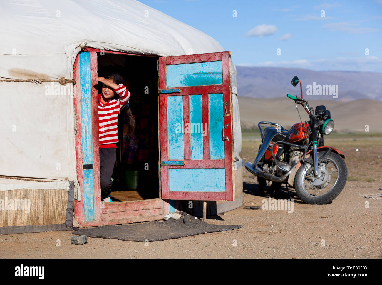 A girl pokes her head out of her family ger tent in the Tsaast Uul Valley in remote western Mongolia. - Stock Image