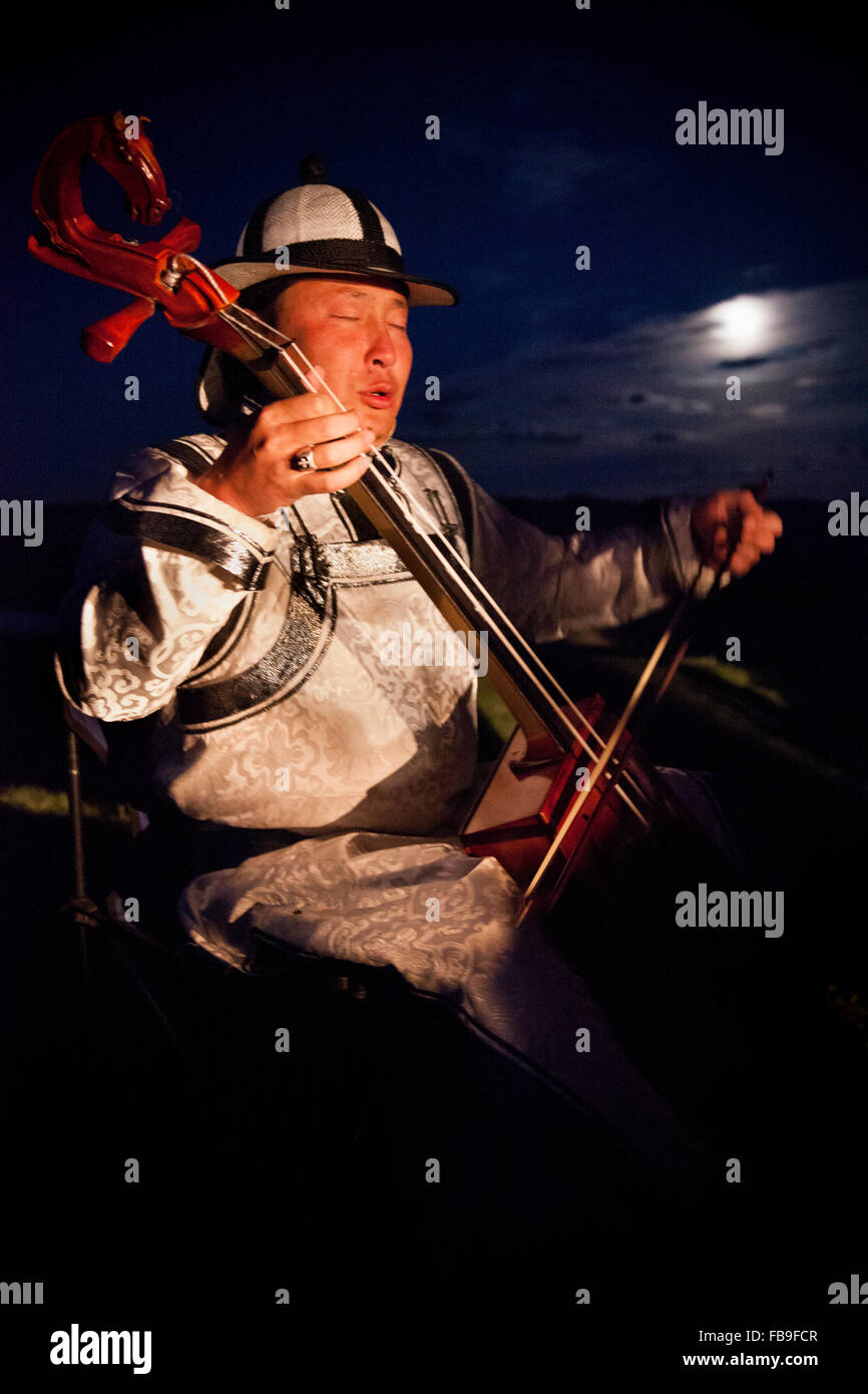 A horse hair fiddler and throat singer conveys the rhythms of horses and steppe life in the moonlight, Mongolia. - Stock Image