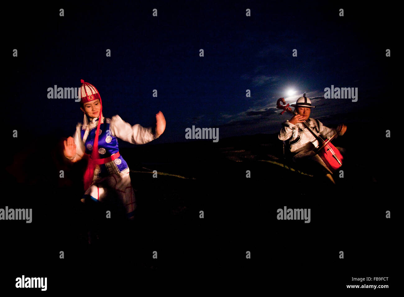 Throat singing, flute, horse hair fiddle and dancing convey the rhythms of horses and steppe life in the moonlight, - Stock Image