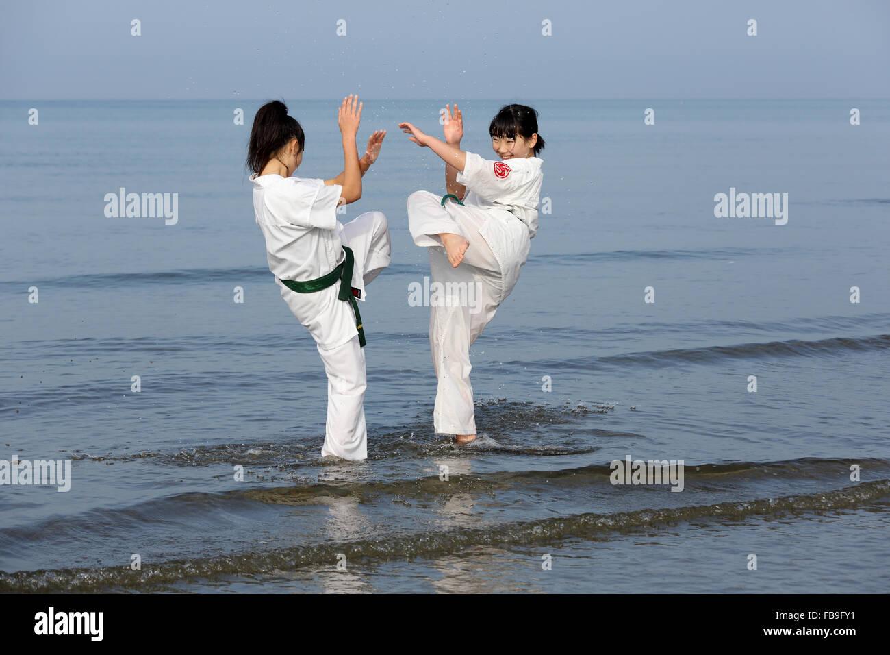Japanese karate girls training of karate in midwinter of a new year at Ichinomiya Beach - Stock Image
