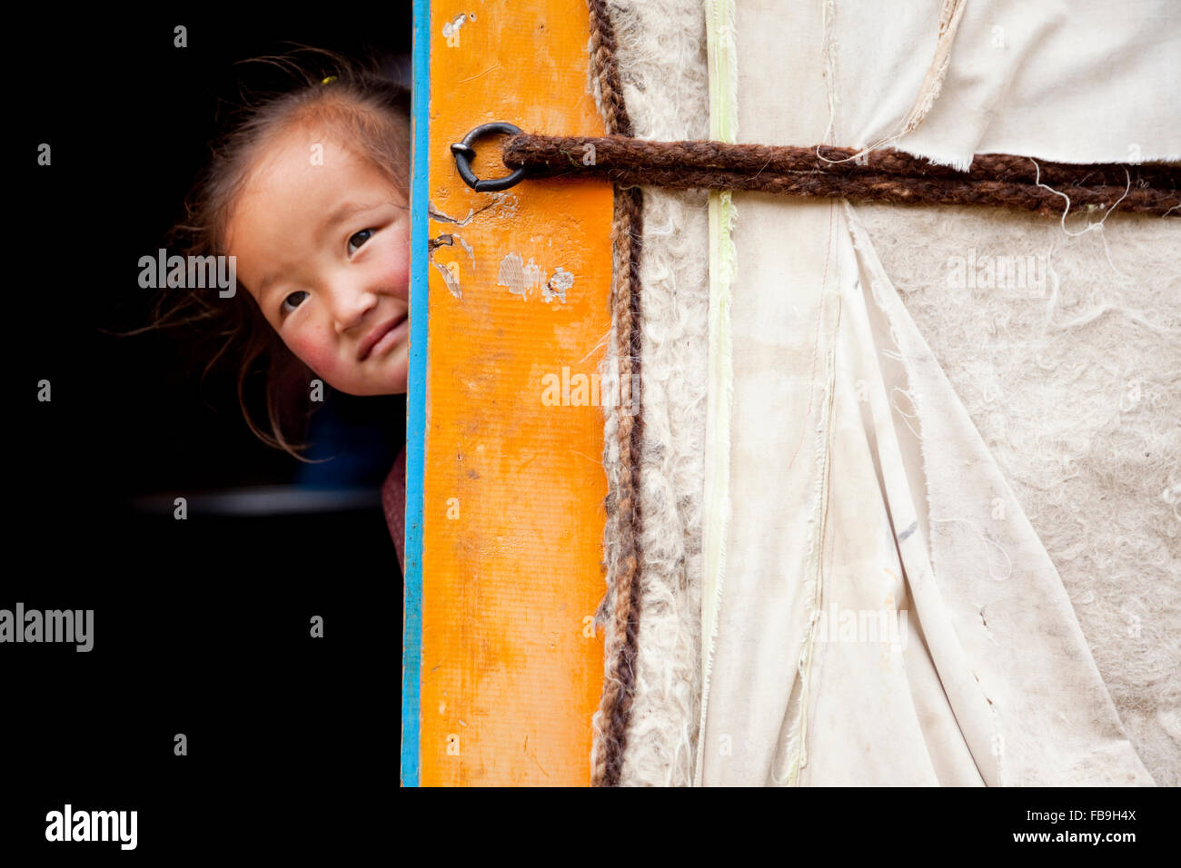 A cheeky young girl pokes her head out from inside her family's ger in Kharkhiraa Turgen National Park, Mongolia. - Stock Image