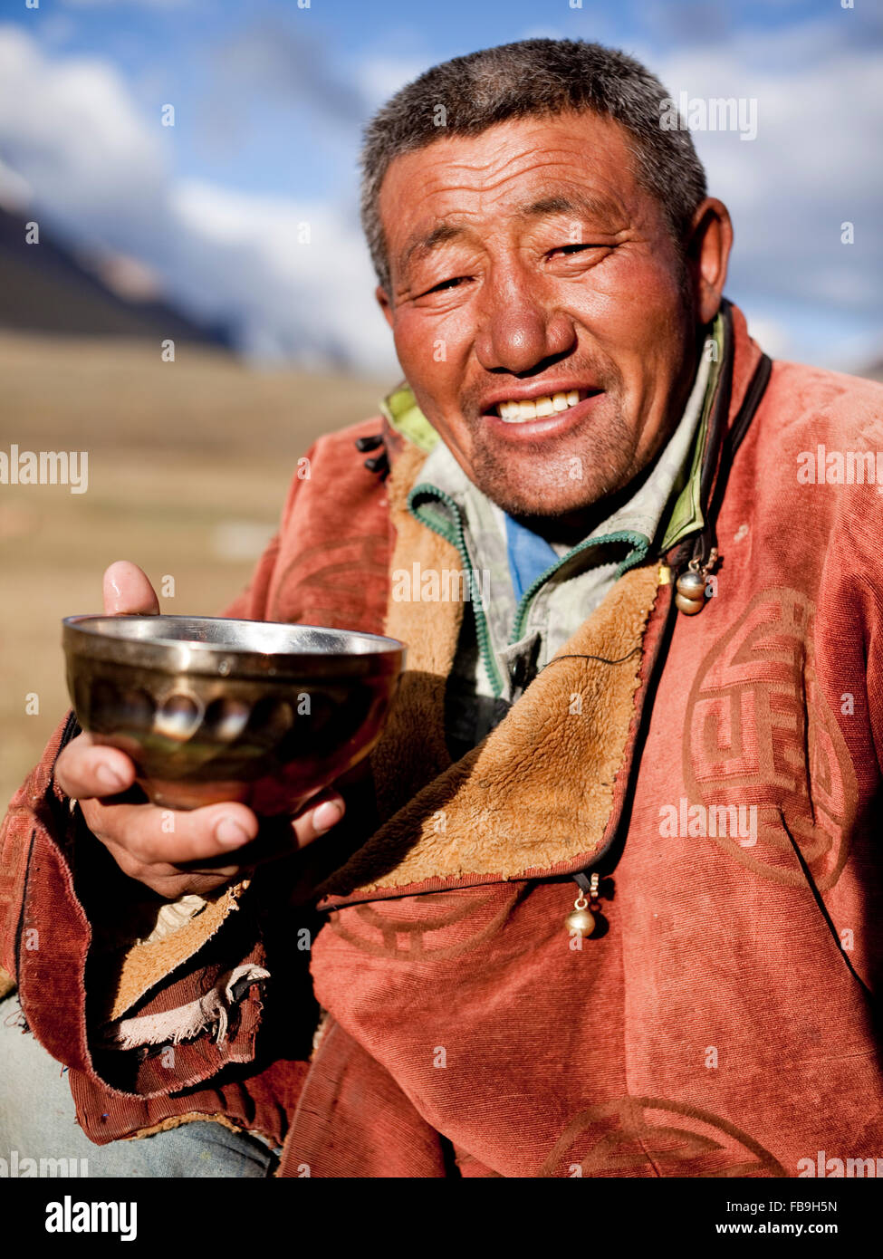 Idesh, a local herder and guide, rests with a hot tea in Kharkhiraa Turgen National Park, Mongolia. - Stock Image