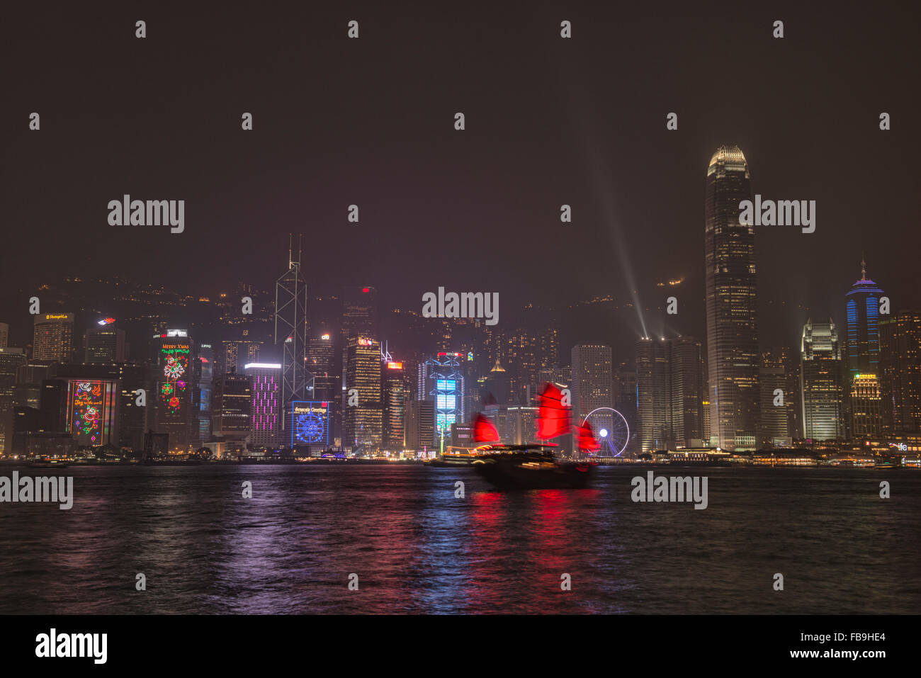 A traditional junk sails through the harbour during A Symphony of Lights in Hong Kong - Stock Image