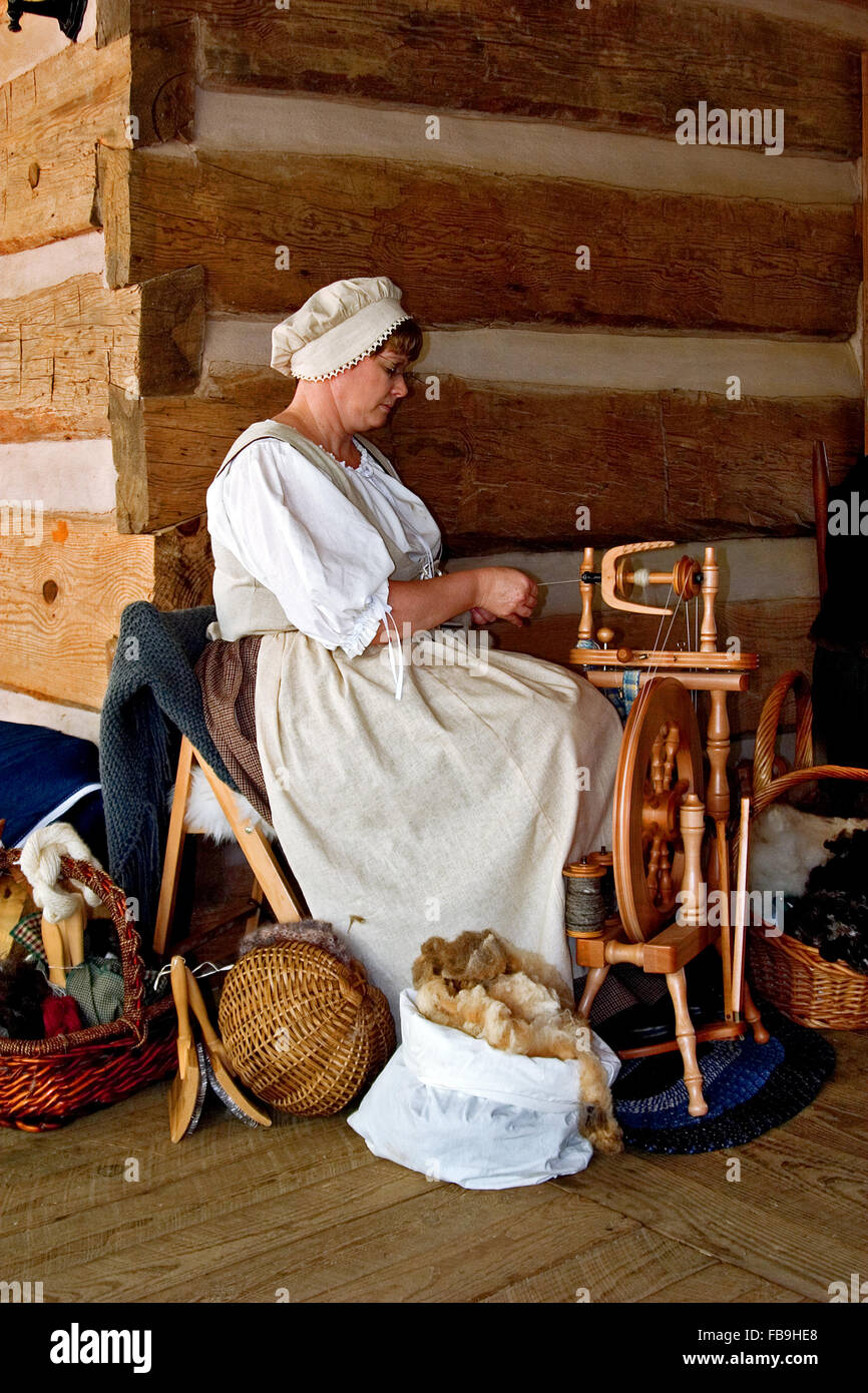 A woman spins wool into thread on a spinning wheel at Red Top Mountain State Park, Georgia, USA. Stock Photo