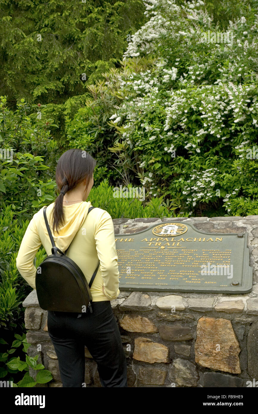 A young hiker reads a trail marker at the start of the Appalachian trail at Amicalola Falls State Park, Georgia, - Stock Image