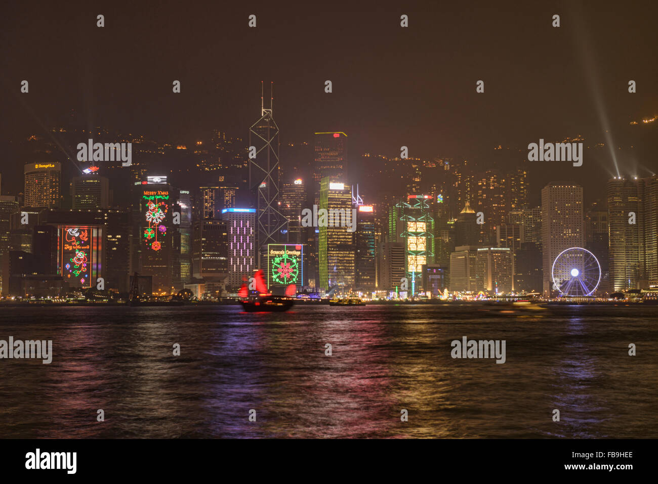 A traditional junk sails through the harbour during A Symphony of Light in Hong Kong - Stock Image