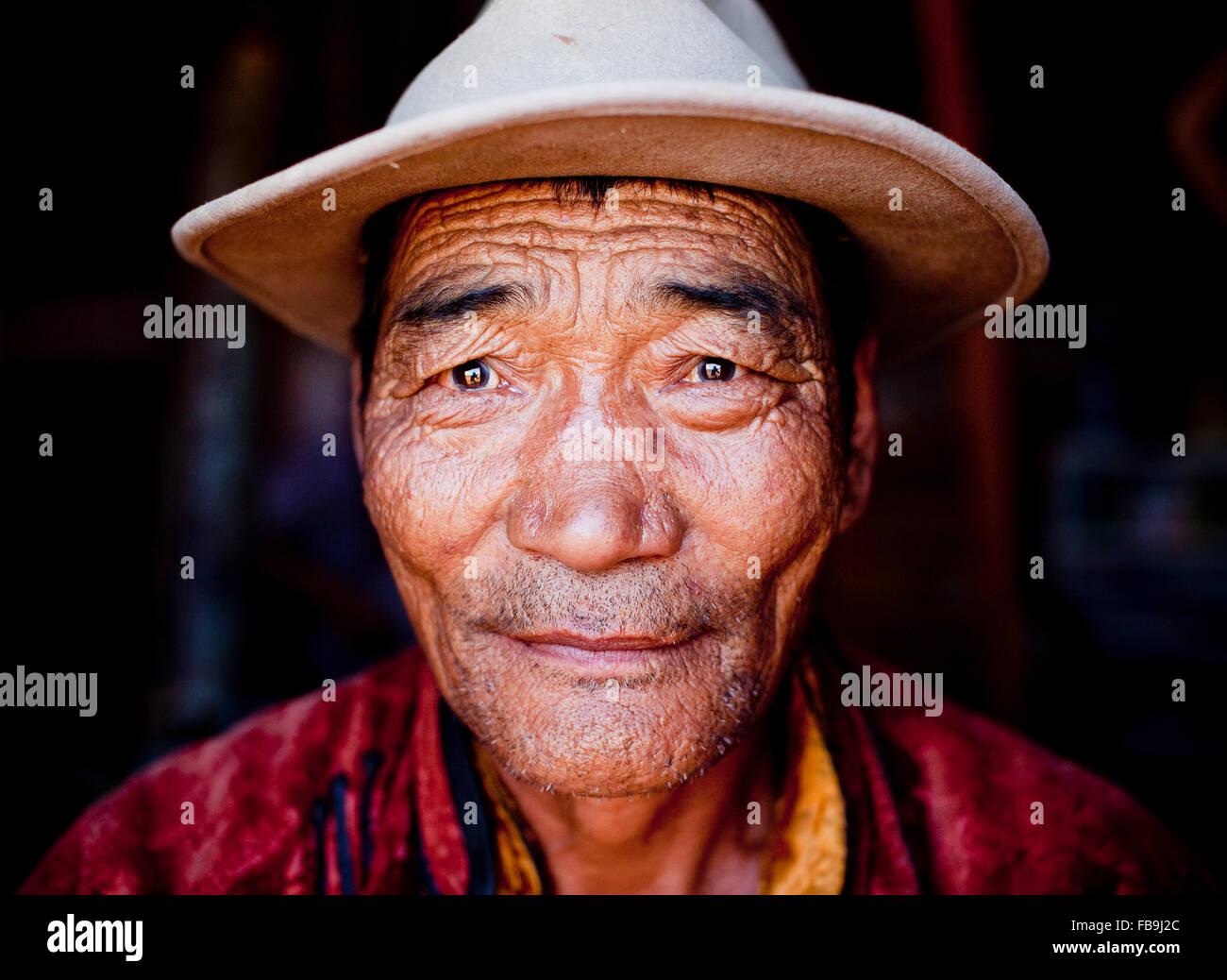 A lifetime spent under the eternal blue sky encapsulated in the face of a nomad elder in Mongolia's Gobi Desert. - Stock Image