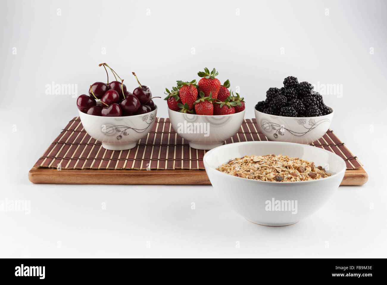 Homemade Granola and Cherries, Strawberries, and Blackberries in ceramic bowls on bamboo mat in the background Stock Photo