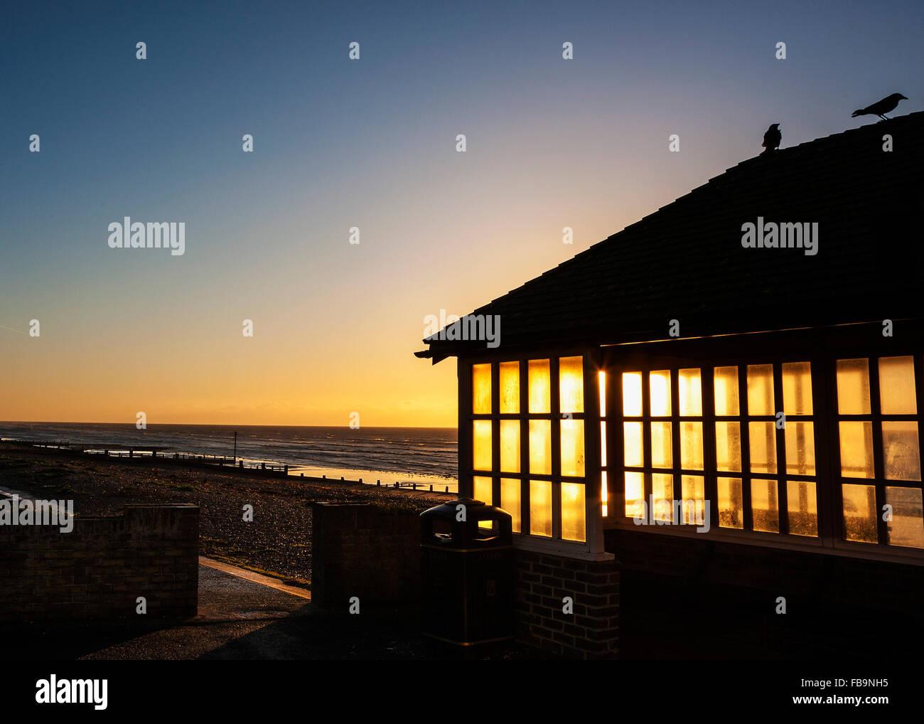 Sunrise through windows of beach shelter - Stock Image