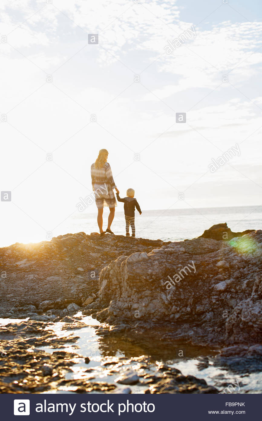 Sweden, Gotland, Faro, Rear view of mother and son (2-3) standing on rocky coast - Stock Image