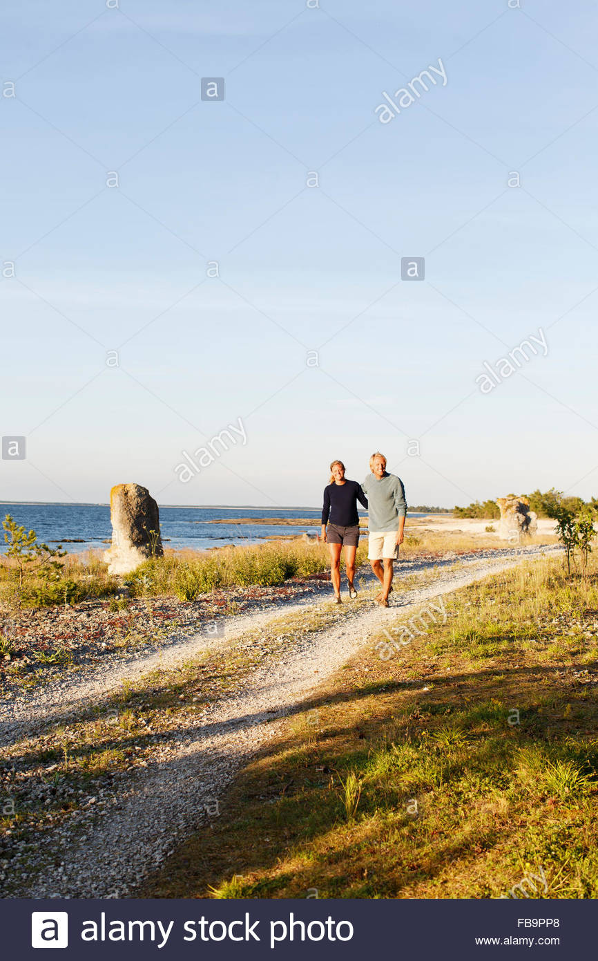Sweden, Gotland, Farosund, Couple walking along seaside - Stock Image