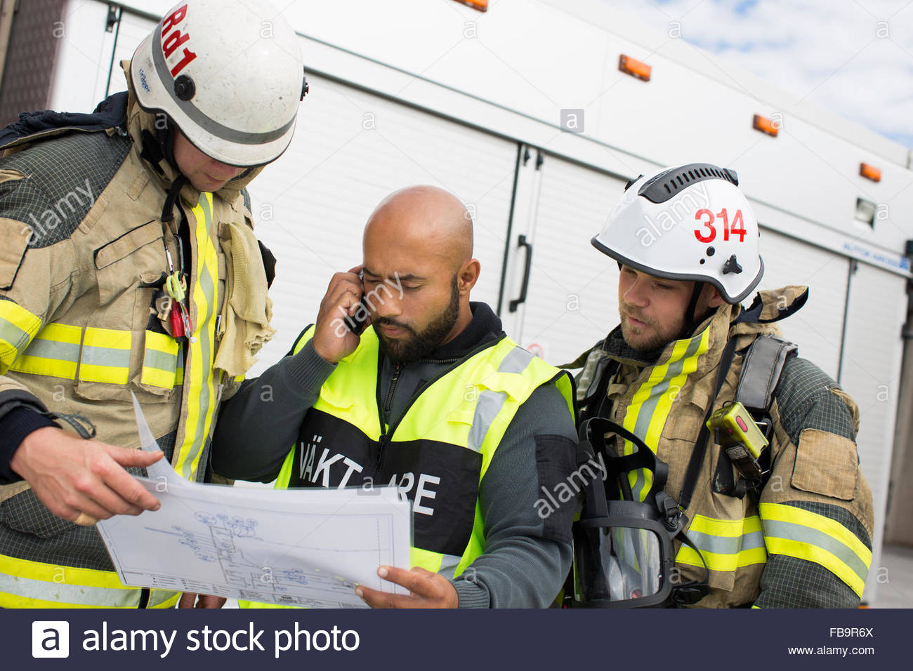 Sweden, Sodermanland, Security guard and firefighters looking at plan - Stock Image