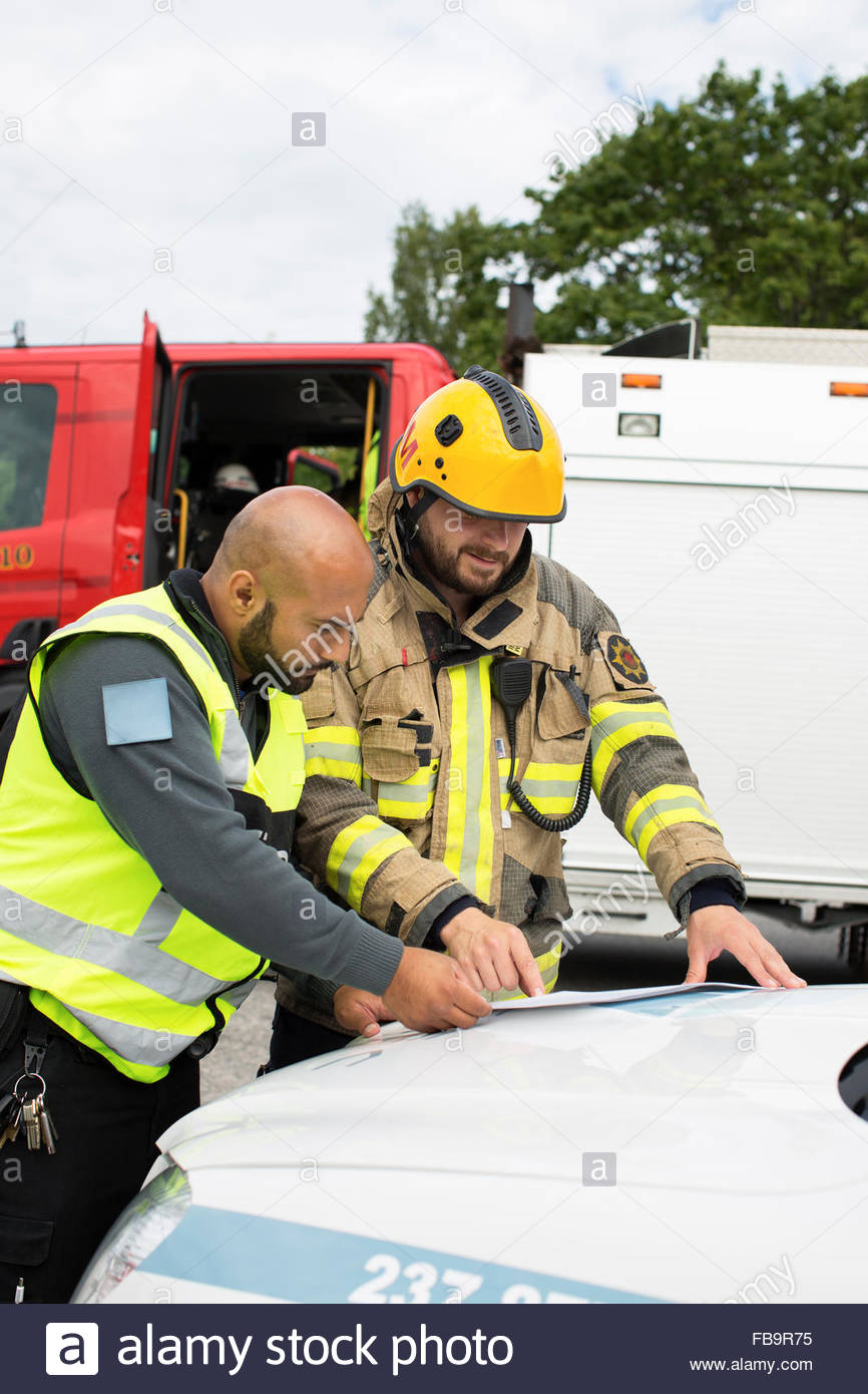 Sweden, Sodermanland, Security guard and firefighter discussing plan - Stock Image