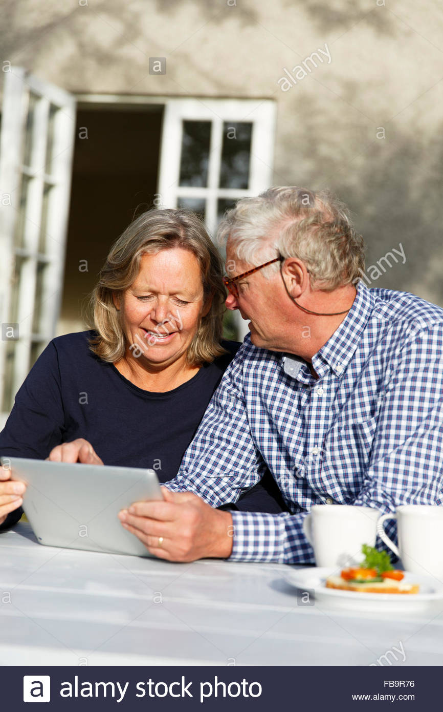 Sweden, Sodermanland, Senior couple discussing finances using digital tablet at table in backyard - Stock Image