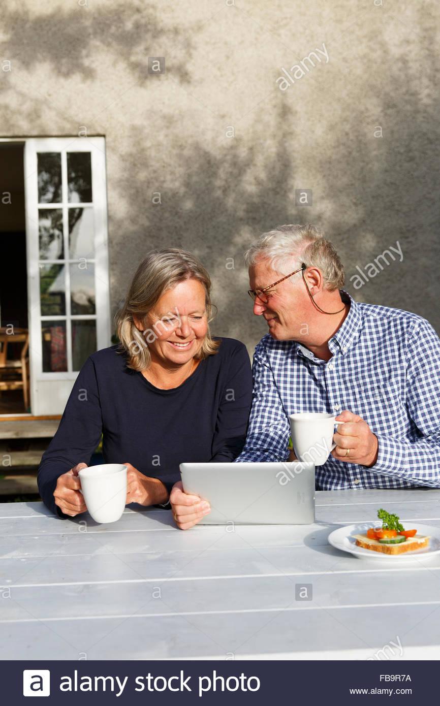 Sweden, Sodermanland, Senior couple doing financial planning using digital tablet at table in backyard - Stock Image
