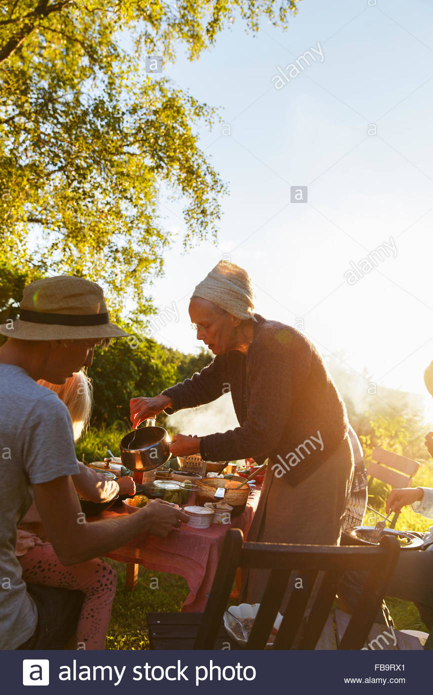 Sweden, Sodermanland, Jarna, Family with small child (4-5) having dinner in backyard at sunset - Stock Image