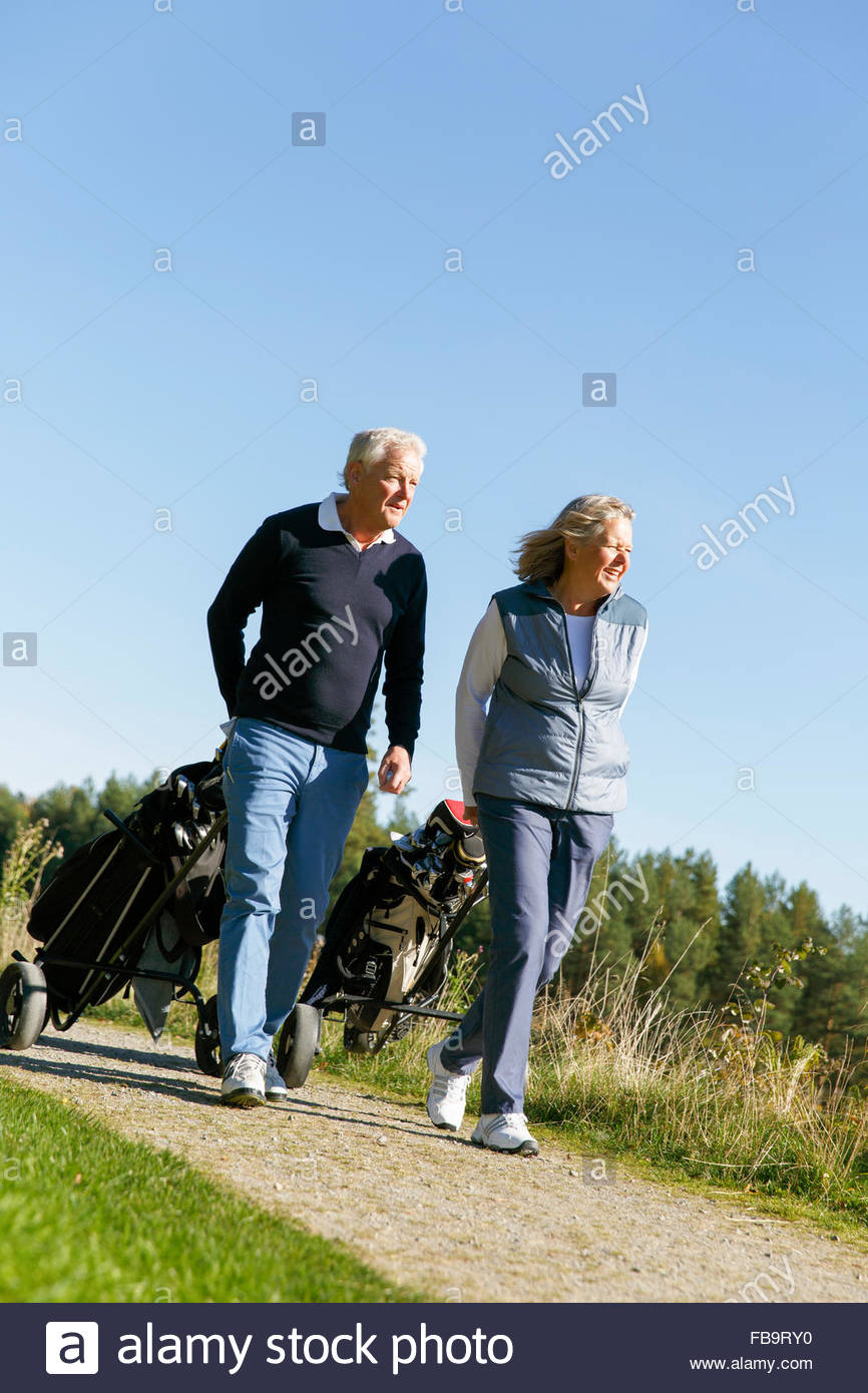 Sweden, Sodermanland, Senior man and mature woman walking with golf bags - Stock Image