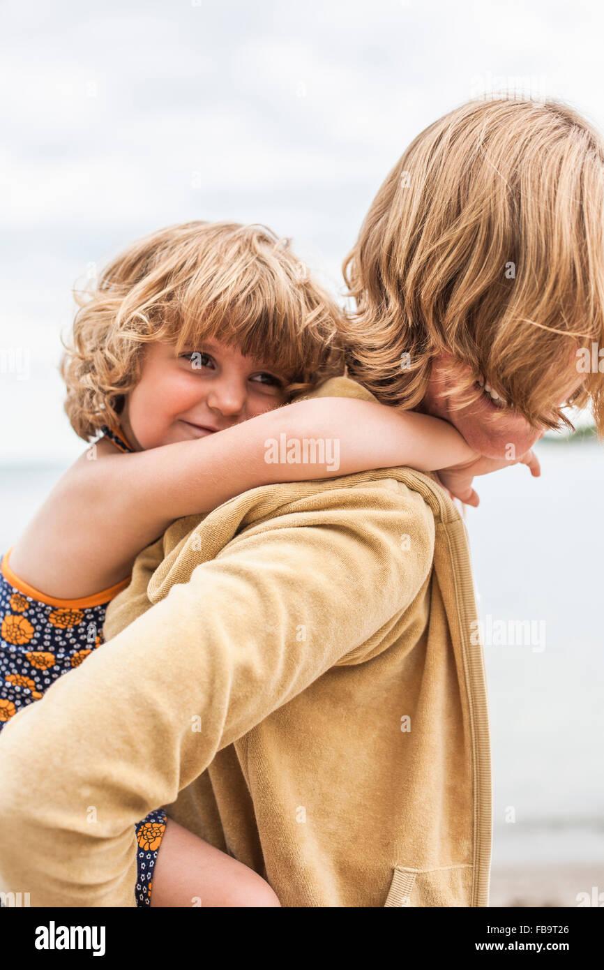 Sweden, Sodermanland, Stockholm Archipelago, Musko, Daughter (4-5) embracing mother - Stock Image