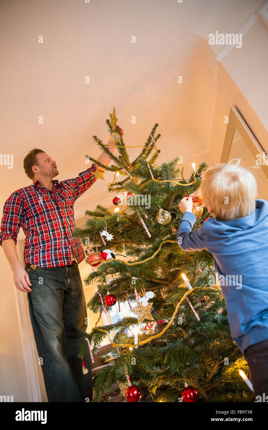 Sweden, Father and son (4-5) decorating Christmas tree - Stock Image