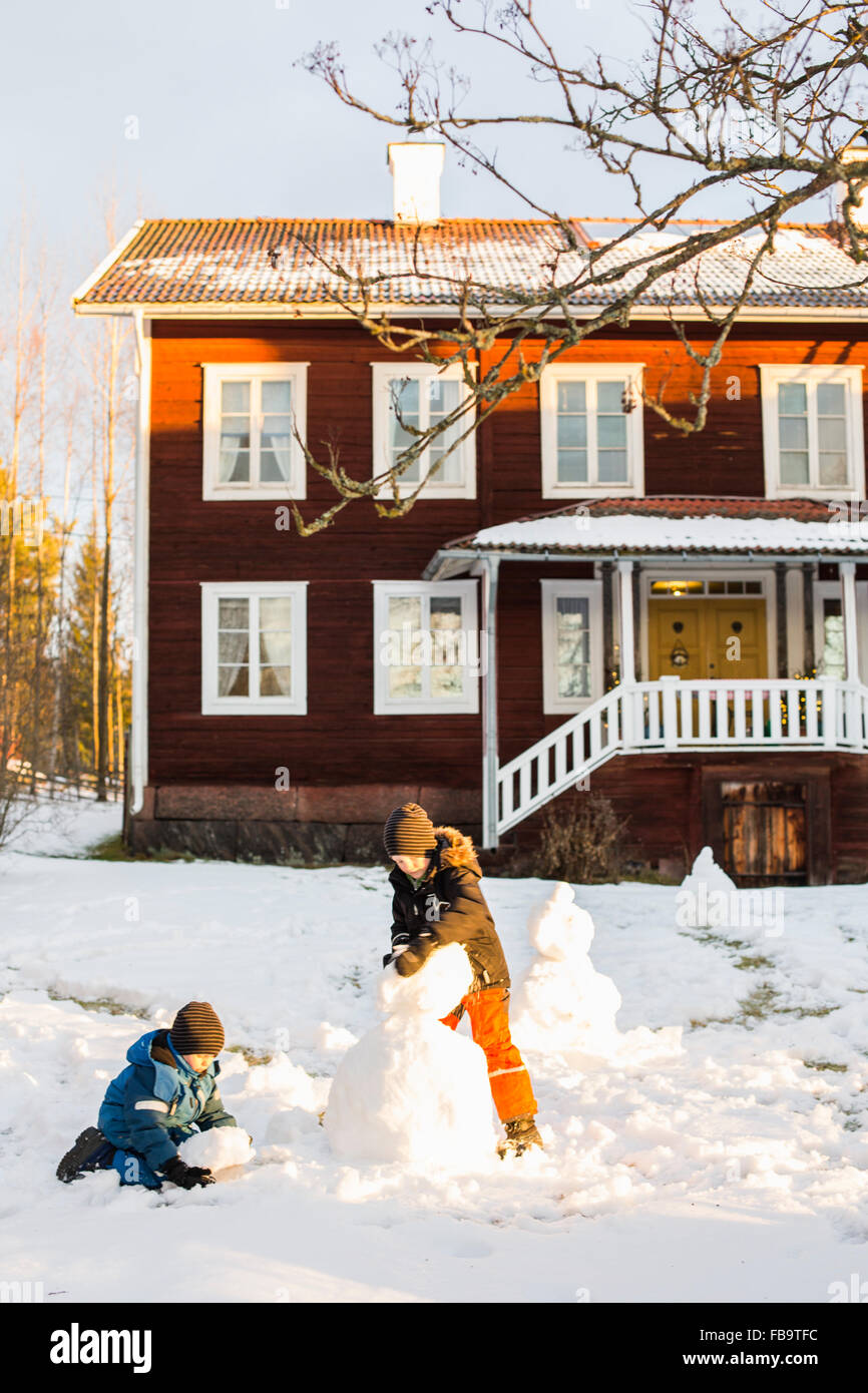 USA, Dalarna, Jarvso, Children (4-5, 6-7) playing with snowman in front of house - Stock Image