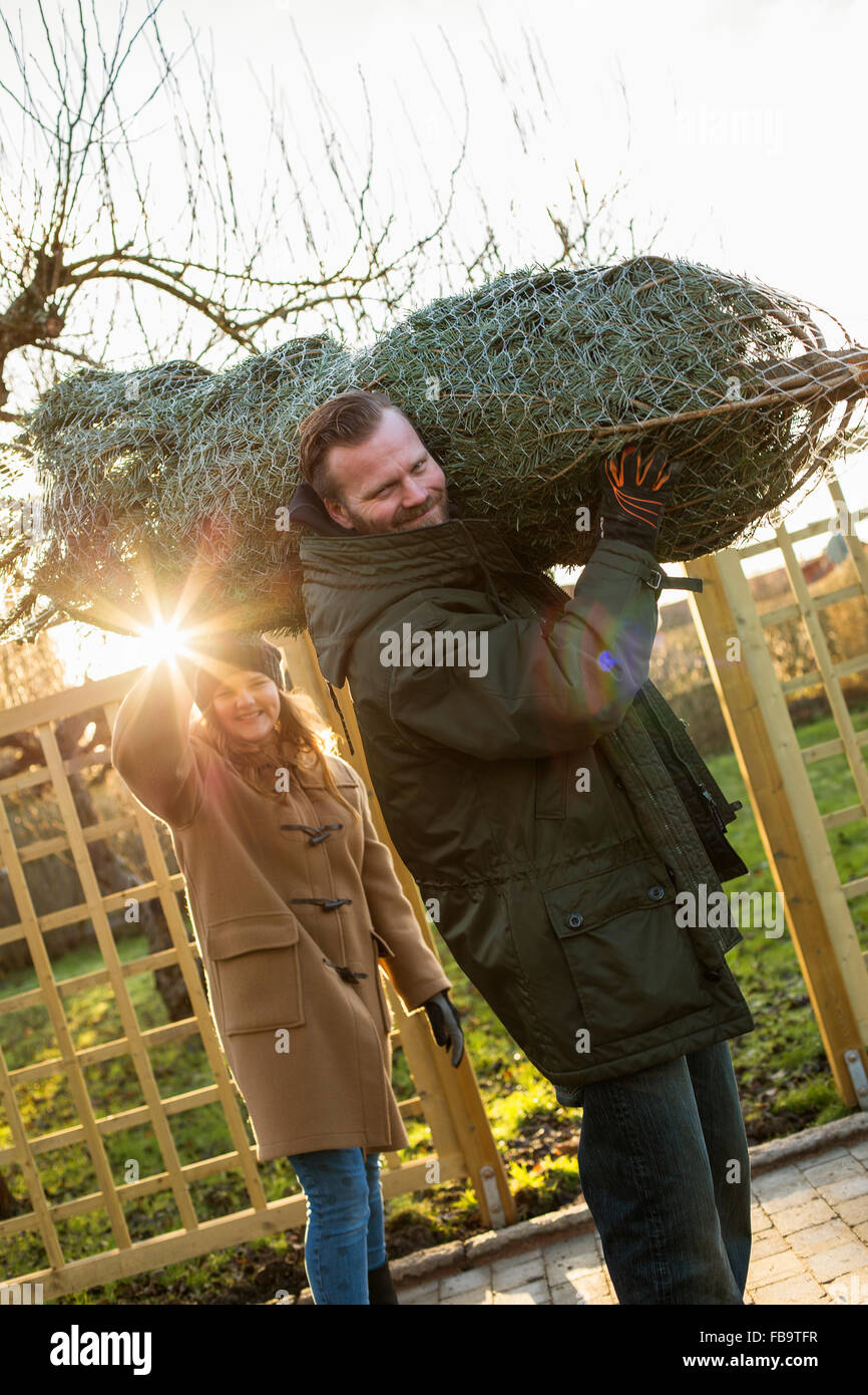 Sweden, Sodermanland, Alvsjo, Man with daughter (12-13) carrying tied up fir tree - Stock Image