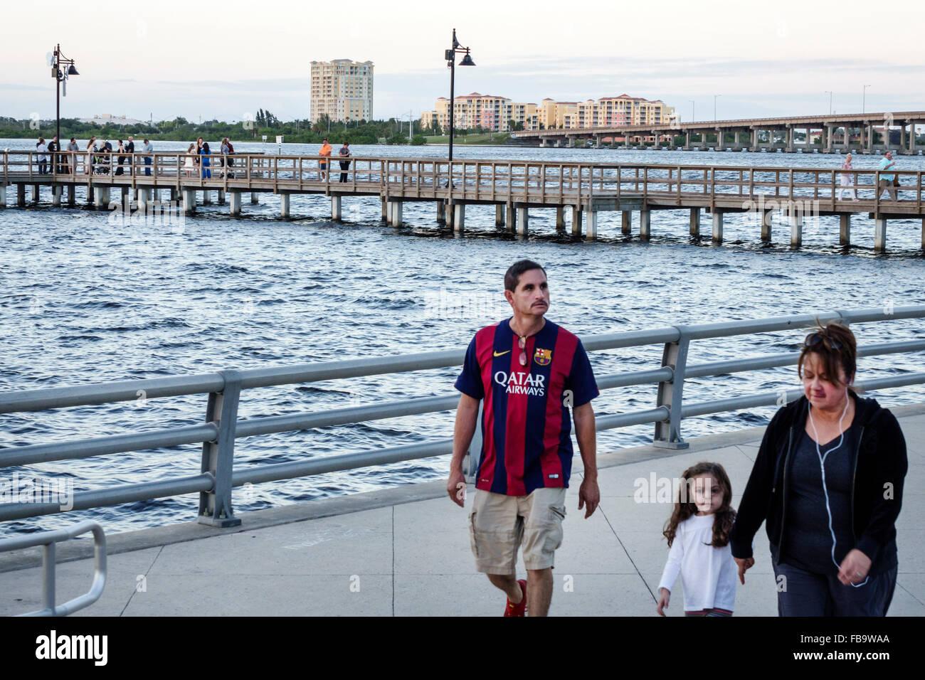 Bradenton Florida Manatee River water Riverwalk Park Green Bridge waterfront Middle Eastern man father woman mother - Stock Image
