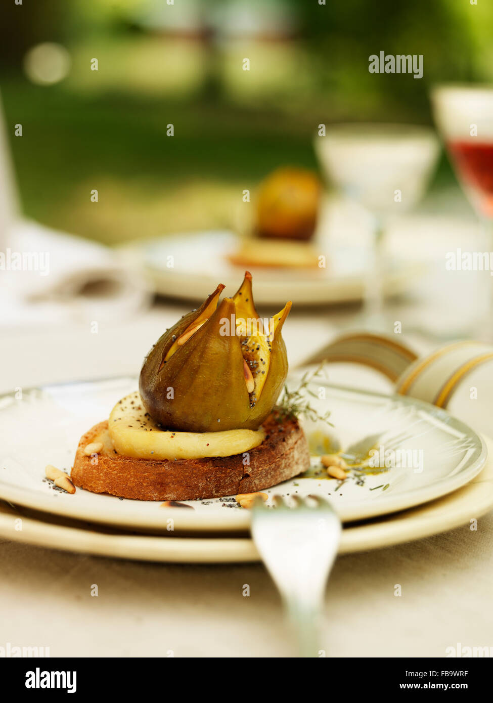 Sweden, Vastergotland, Bread with figs on chevre cheese and with some pine nuts - Stock Image