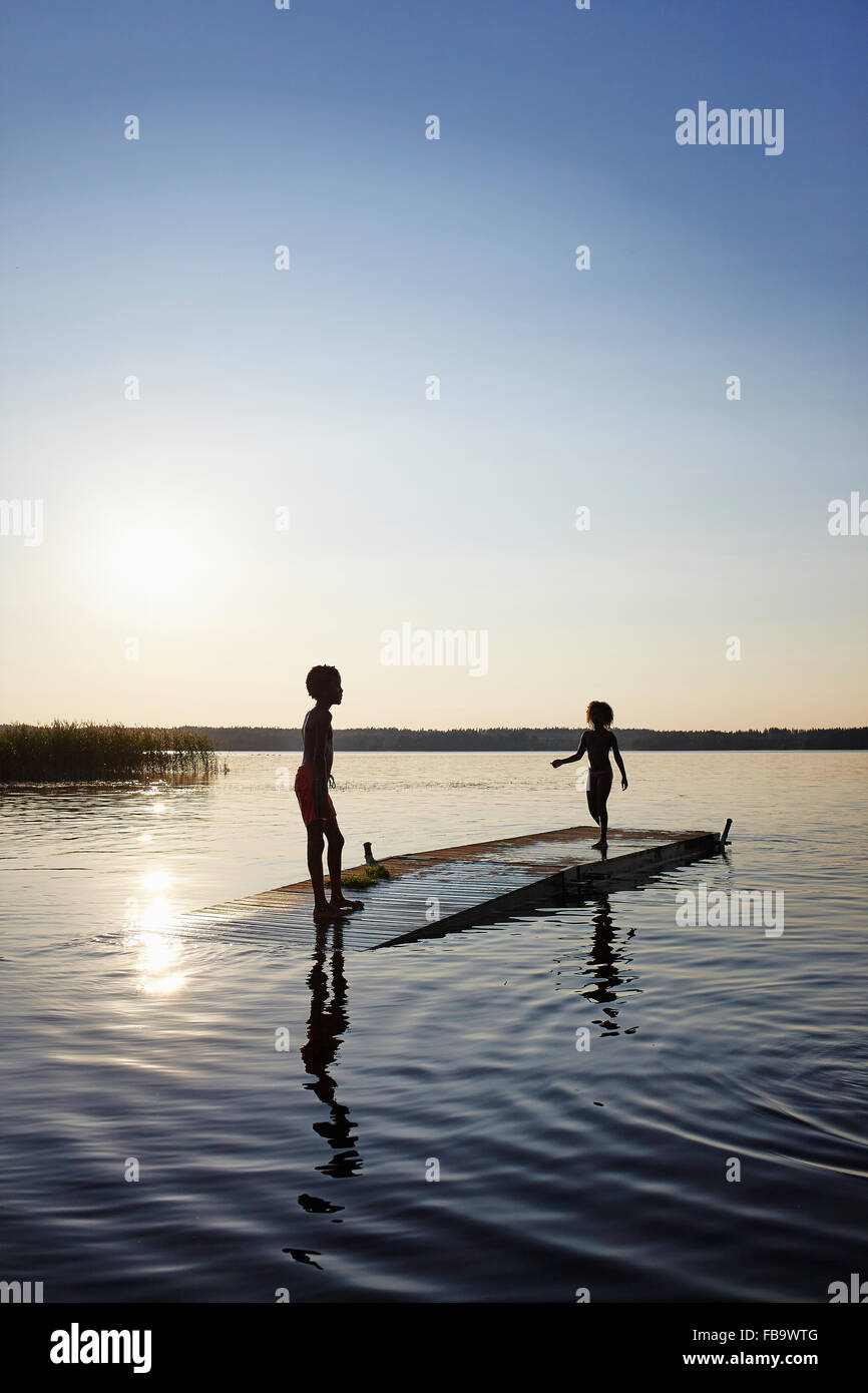 Sweden, Vastra Gotaland, Skagern, Children (6-7, 10-11) swimming in lake - Stock Image