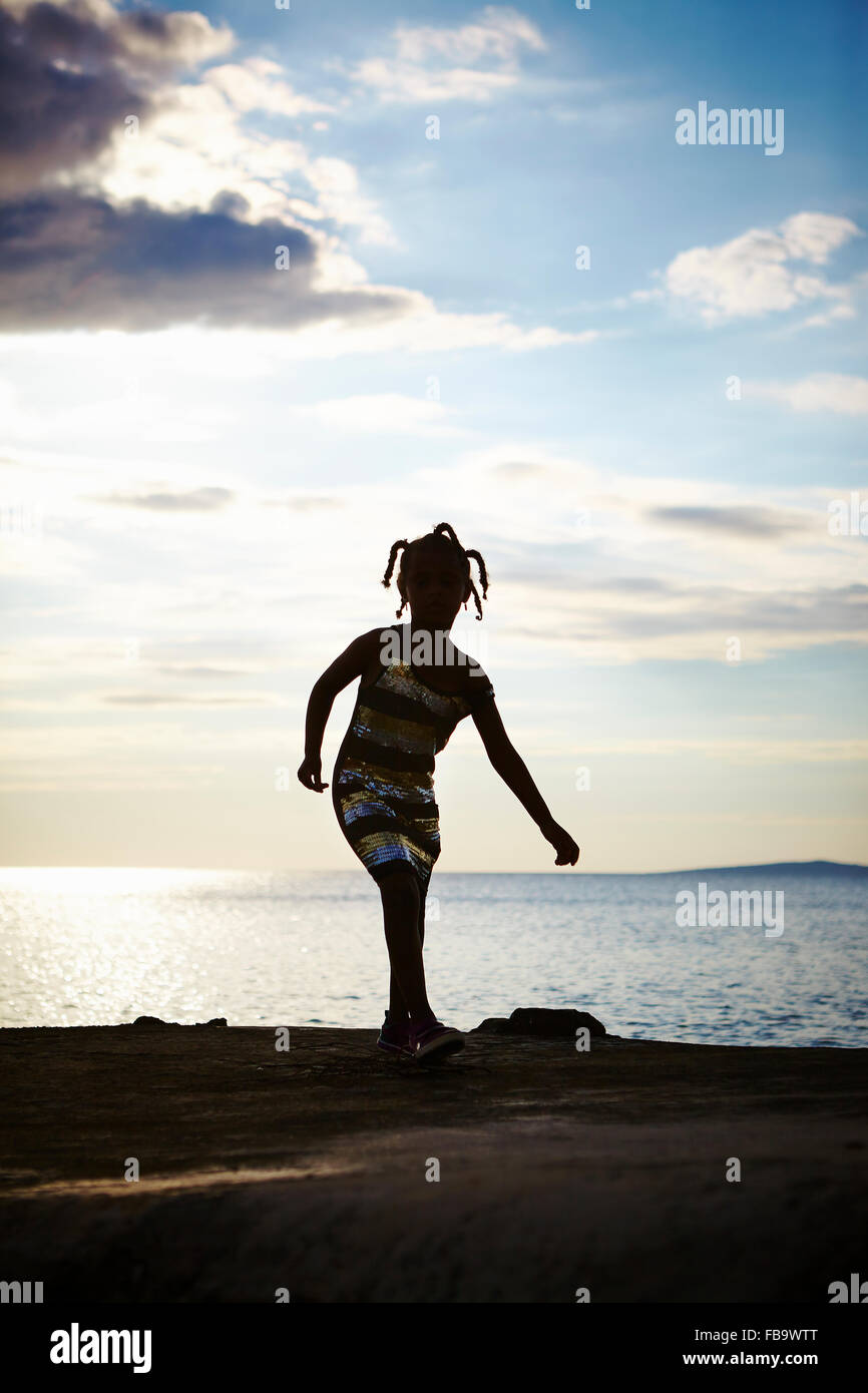 Croatia, Dalmatia, Silba, Silhouette of girl (6-7) playing on sea coast - Stock Image