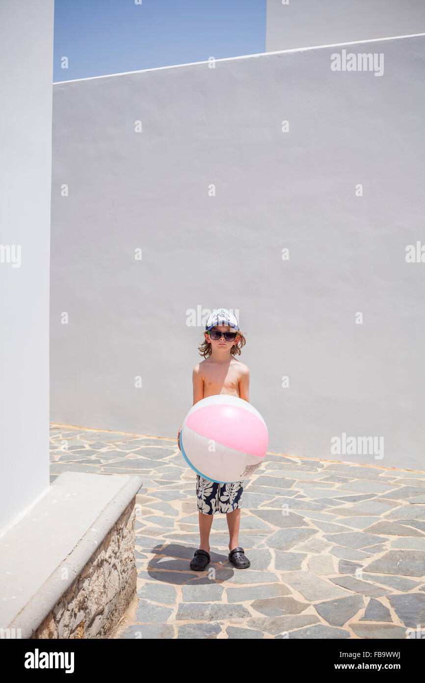 Greece, Karpathos, Amopi, Boy (8-9) standing with ball - Stock Image