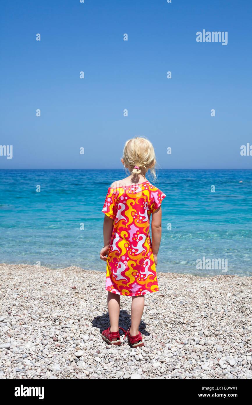 Greece, Karpathos, Amopi, Girl (6-7) standing on beach - Stock Image