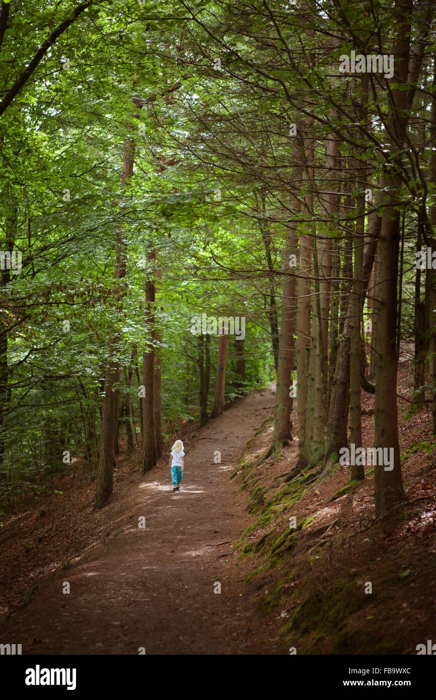 Sweden, Skane, Kockenhus, Girl (6-7) walking in forest - Stock Image