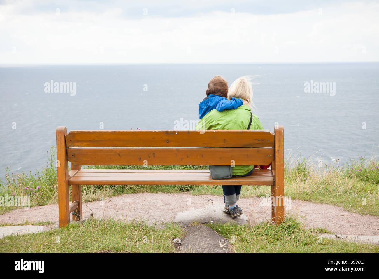 Sweden, Skane, Kullaberg, Kullen, Mother and son (8-9) sitting on beach and looking at sea - Stock Image