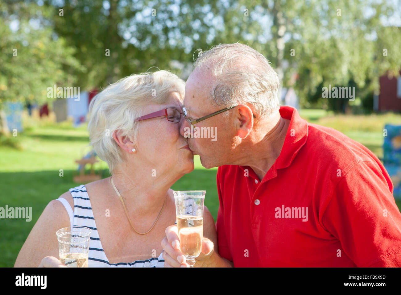 Sweden, Senior couple toasting with champagne flute and kissing - Stock Image