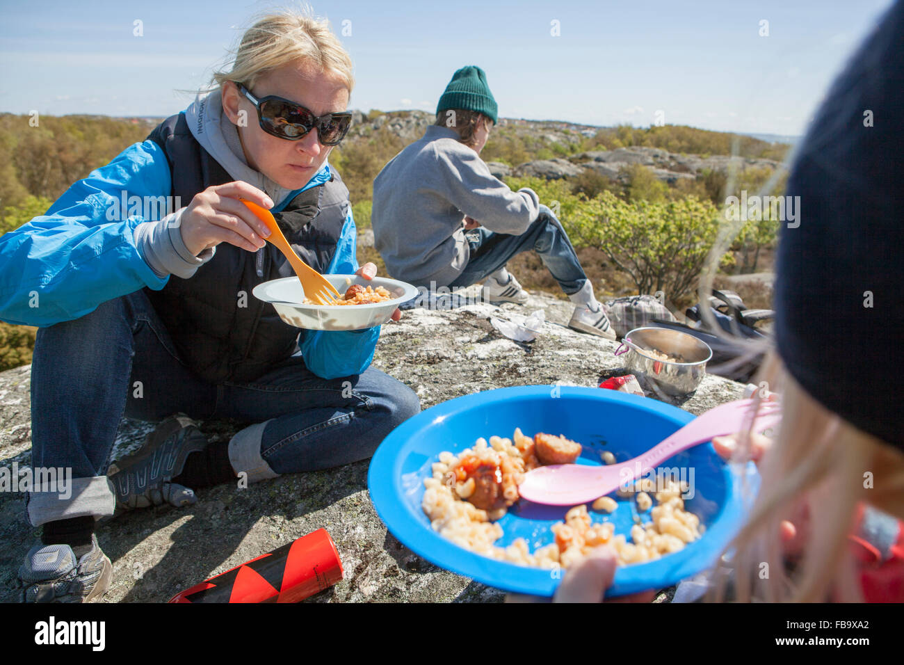Sweden, Gothenburg Archipelago, Vastergotland, Styrso, Mom and her two kids (8-9, 10-11) eating pasta and camping - Stock Image