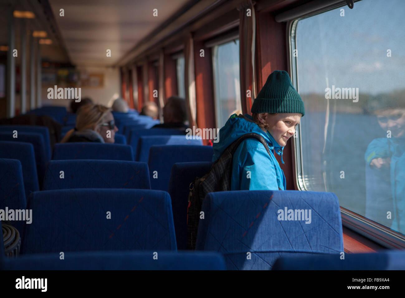 Sweden, Gothenburg Archipelago, Vastergotland, Styrso, Boy (10-11) looking through train window - Stock Image