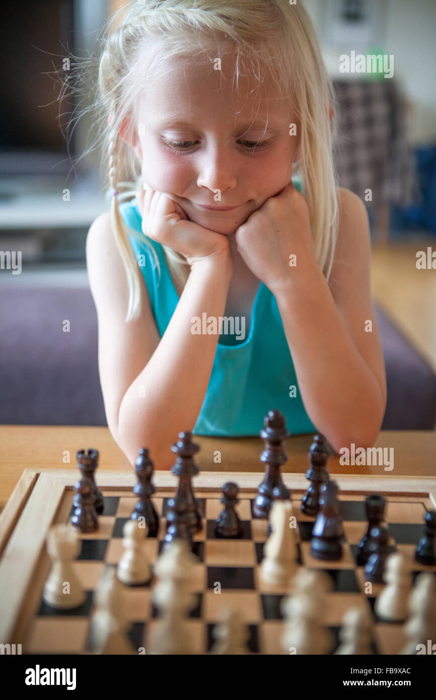 Sweden, Vastergotland, Lerum, Girl (8-9) playing chess in living room - Stock Image