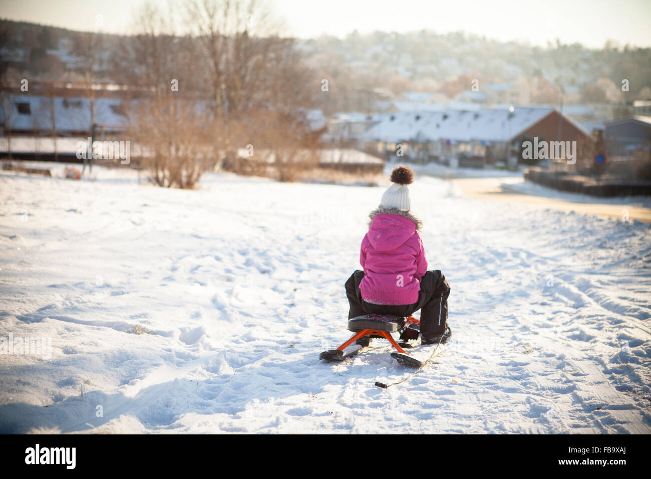 Sweden, Vastergotland, Lerum, Rear view of girl (8-9) sledding along snowy road with townscape in background - Stock Image