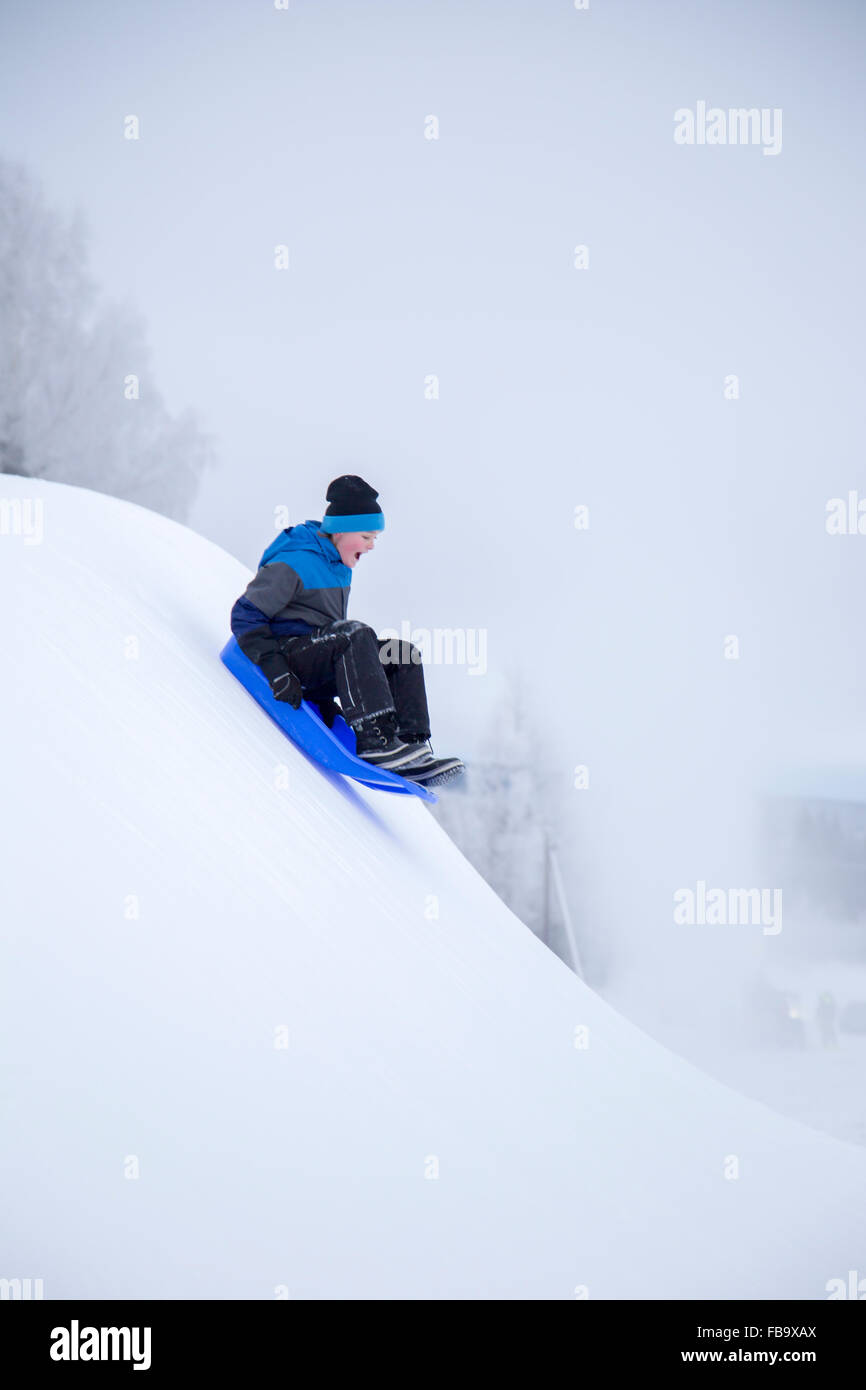 Sweden, Varmland, Sunne, Boy (12-13) sledding down snowy hill - Stock Image