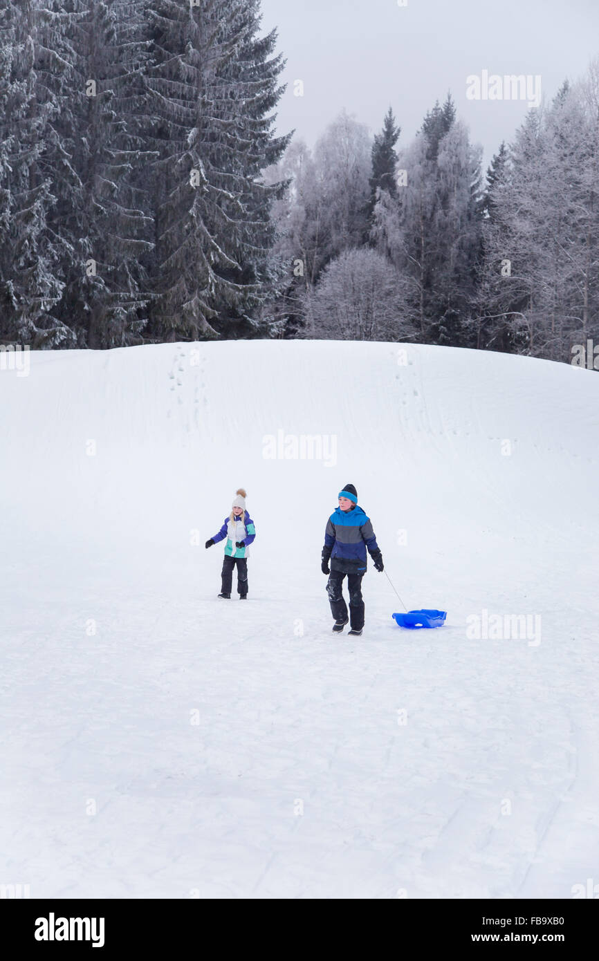 Sweden, Varmland, Sunne, Children (10-11, 12-13) playing on snowy hill - Stock Image