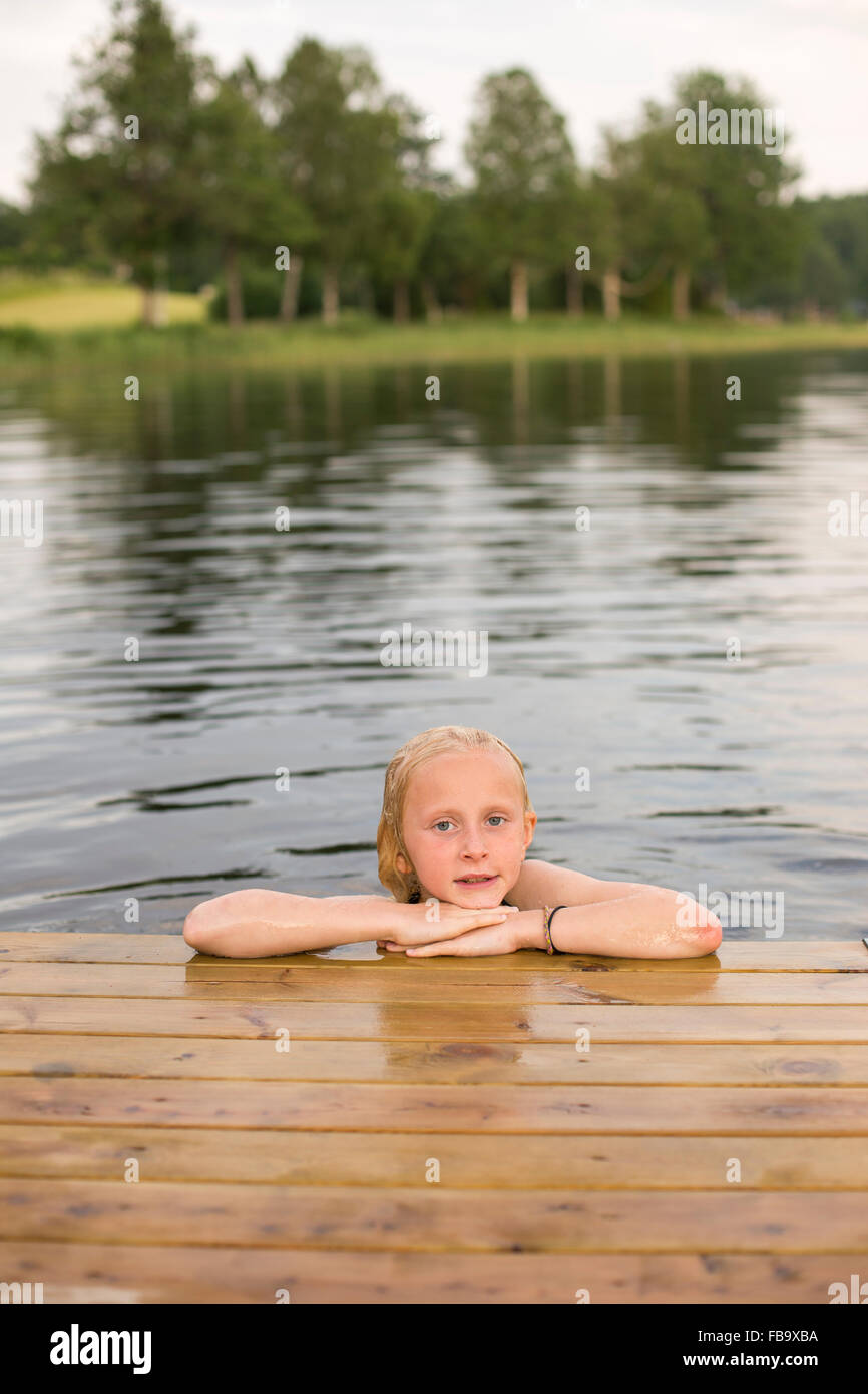 Sweden, Smaland, Braarpasjon, Portrait of girl (10-11) in lake with hands on chin - Stock Image