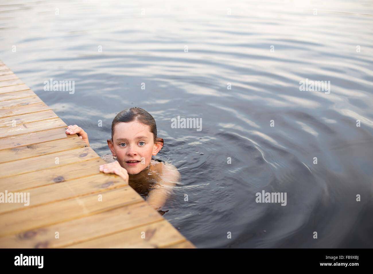 Sweden, Smaland, Braarpasjon, Portrait of boy (12-13) in lake touching wooden jetty - Stock Image