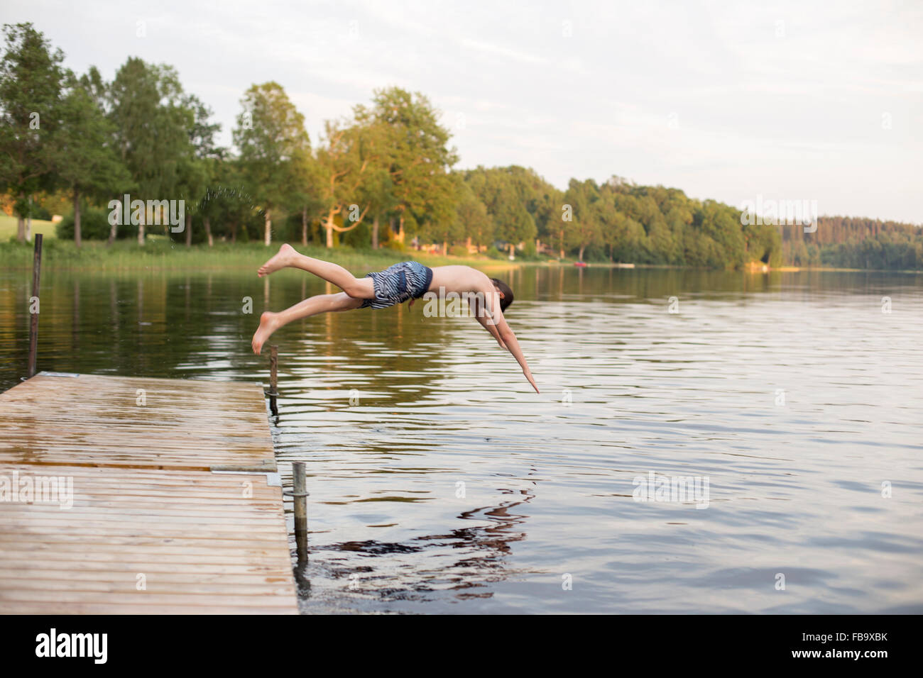 Sweden, Smaland, Braarpasjon, Boy (12-13) jumping into lake from jetty - Stock Image