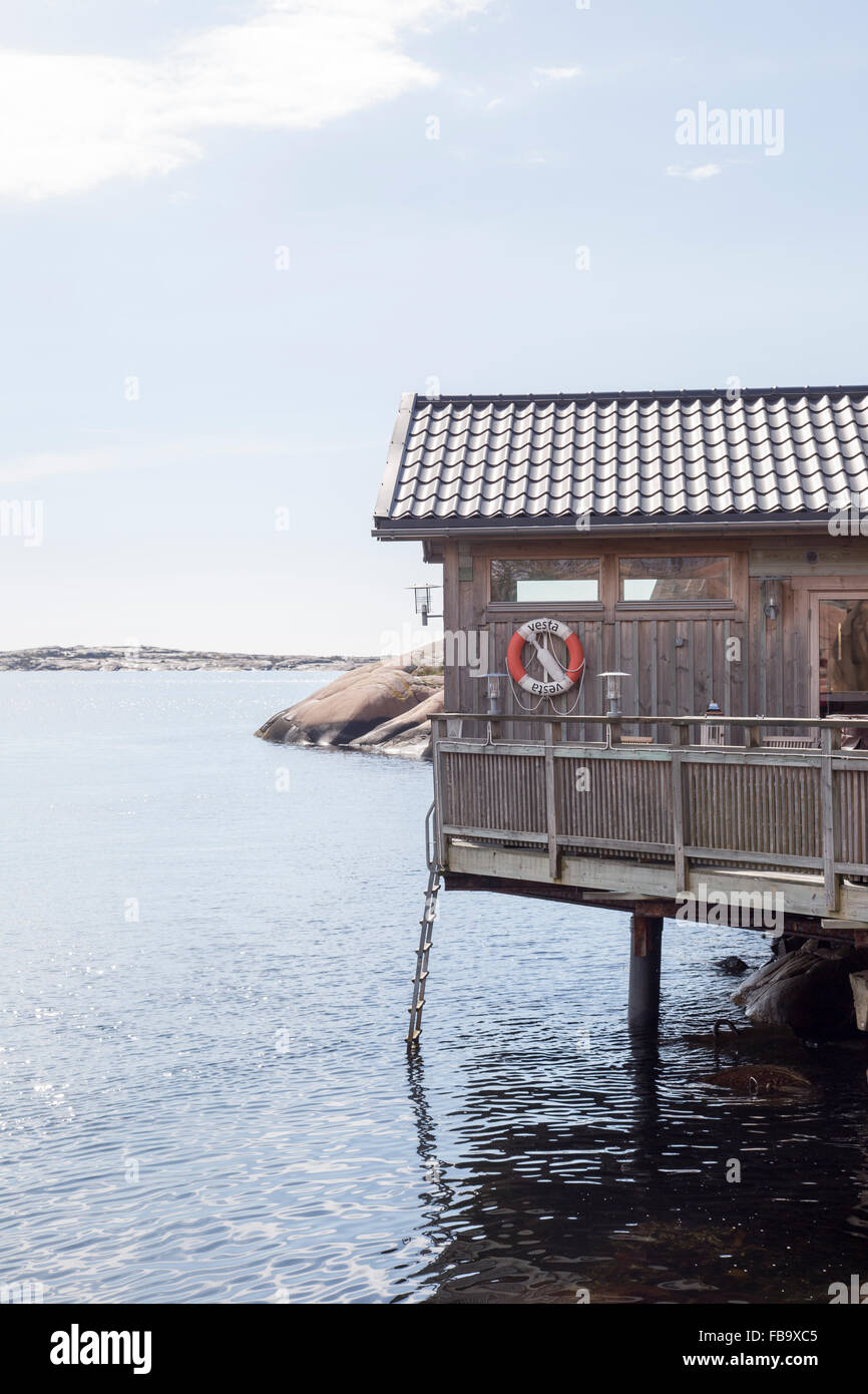 Sweden, West Coast, Bohuslan, Lysekil, Wooden hut with lifebelt on wall over sea - Stock Image