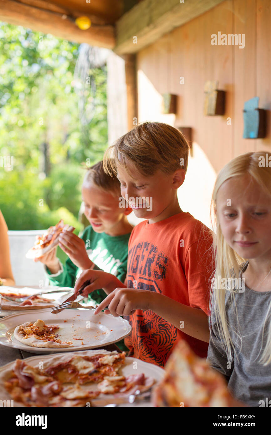 Sweden, Skane, Brothers (8-9) and sister (10-11) eating pizza at family dinner - Stock Image