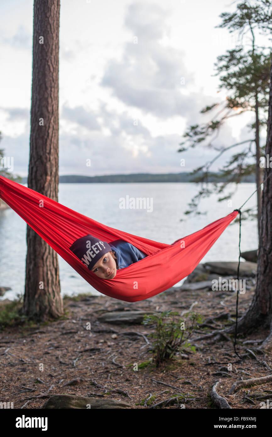 Sweden, Vastergotland, Lerum, Boy (12-13) lying in hammock by lake Harsjon at sunset - Stock Image