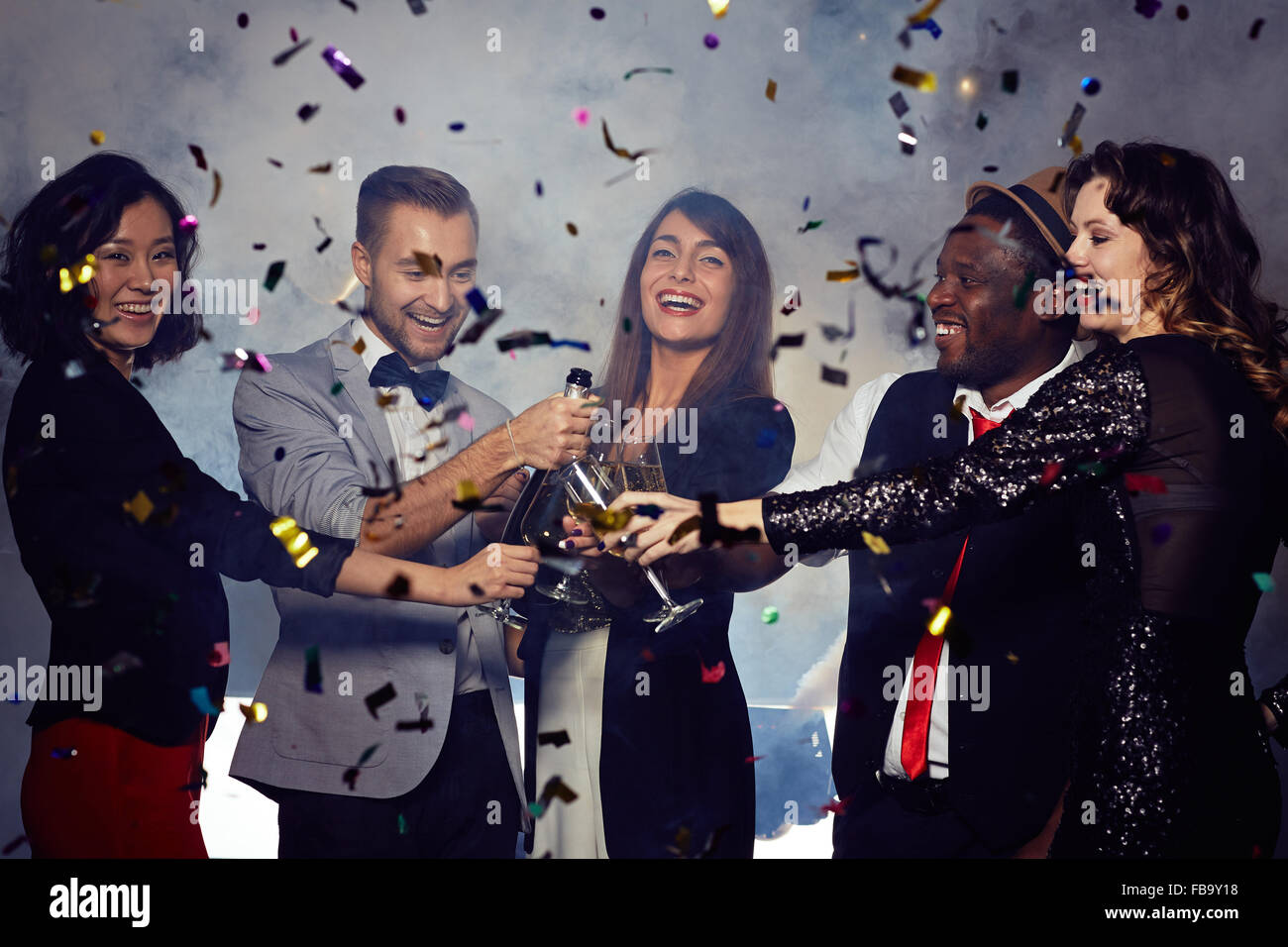 Cheerful friends toasting with champagne at New Year's Eve party - Stock Image