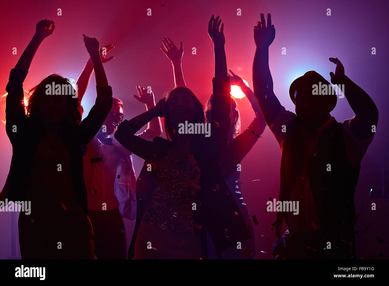Young people raising their arms in dance - Stock Image